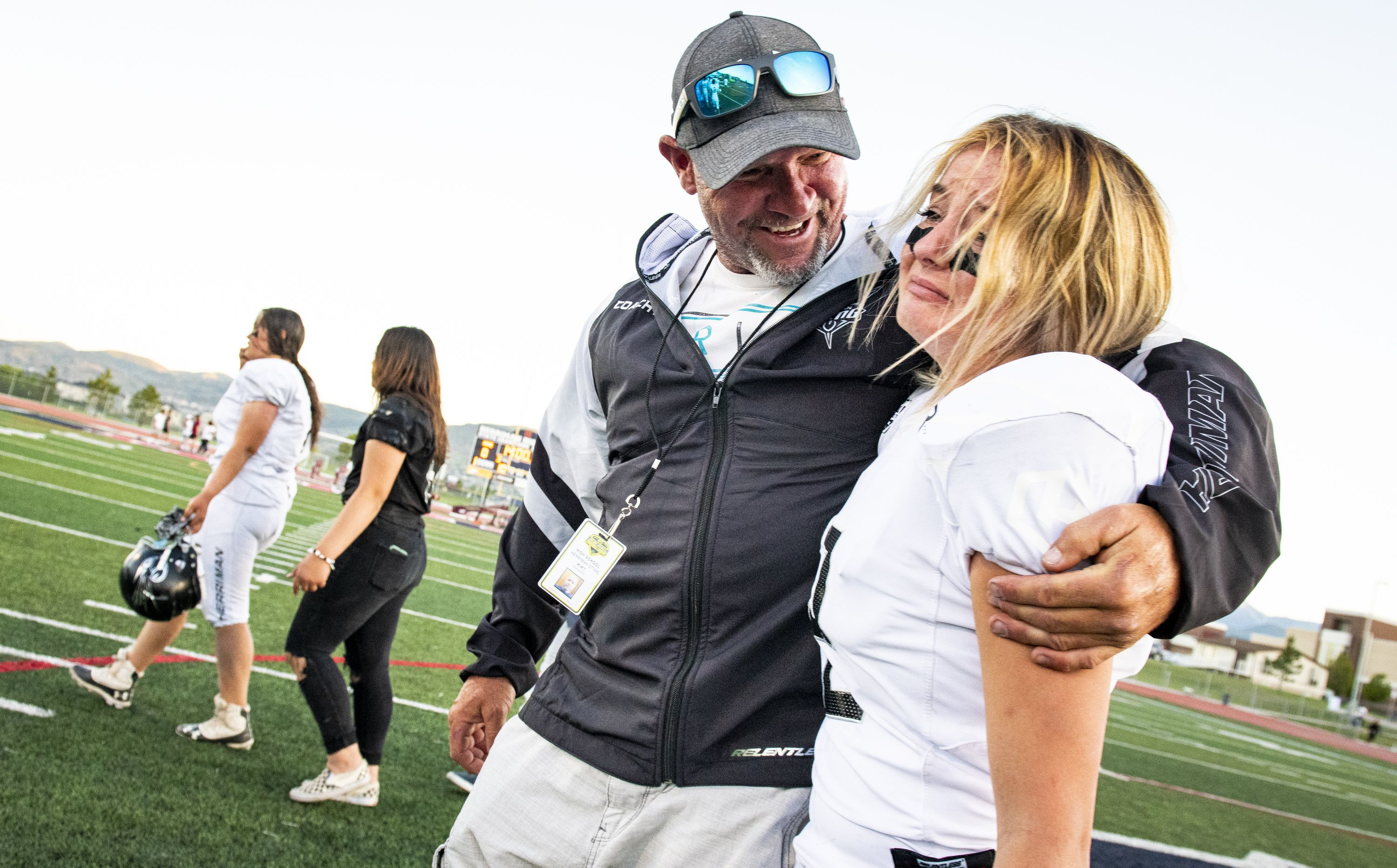 (Isaac Hale   Special to The Tribune) Herriman's Sydni Ohmie (2) is consoled after the Herriman Sting was defeated by the Kearns Cougars during the second game of the Utah Girls Tackle Football League Championships held at Herriman High School on Thursday, May 27, 2021.