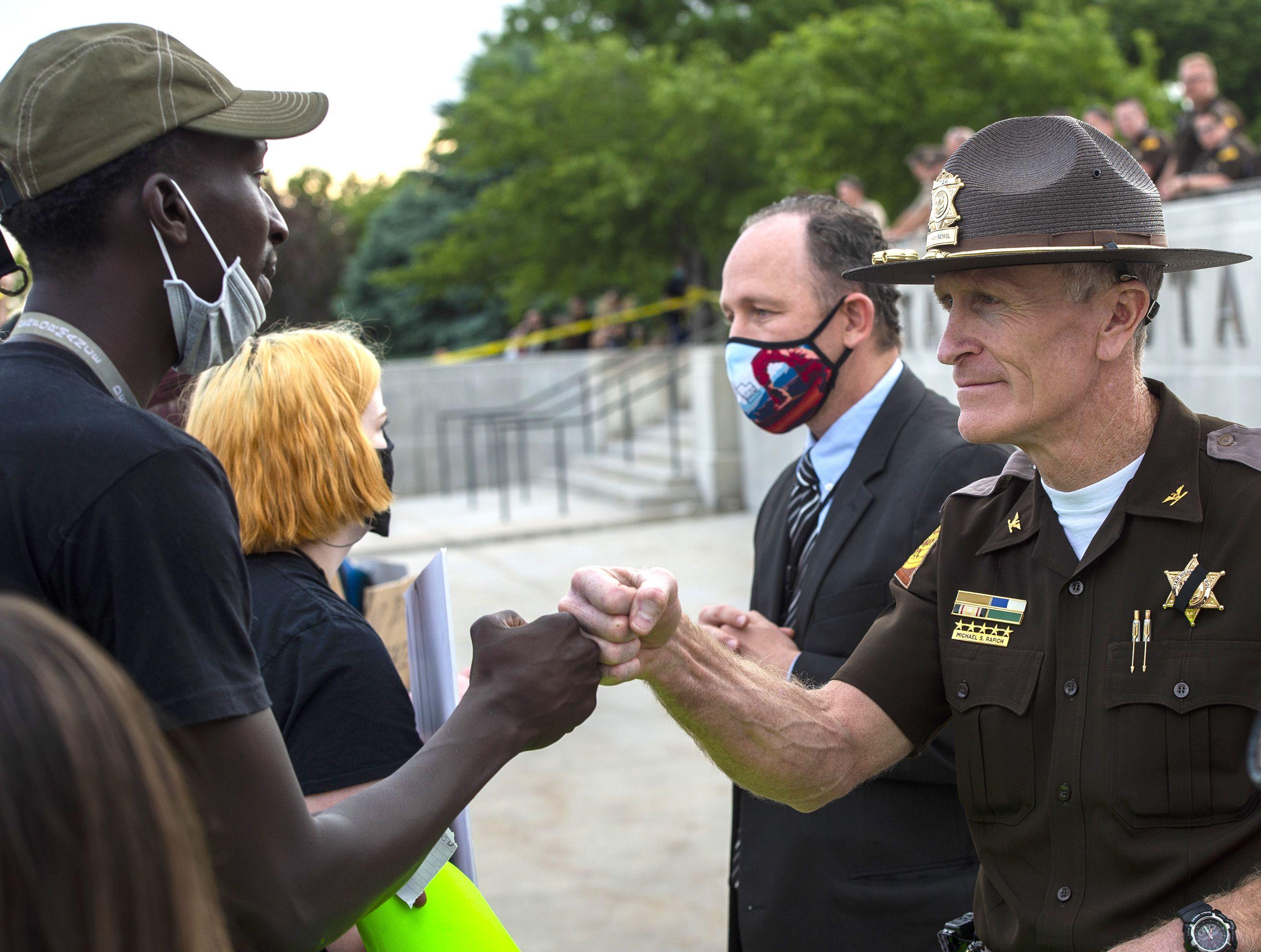 (Rick Egan  |  The Salt Lake Tribune) BK Guajain fist bumps Utah Highway Patrol Major, Michael Rapich in front of the  the State Capitol, during a George Floyd demonstration in Salt Lake City on Thursday, June 4, 2020.