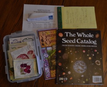 Items needed in determining what seeds to order for the coming garden: catalogs, leftover seeds, and planning notes