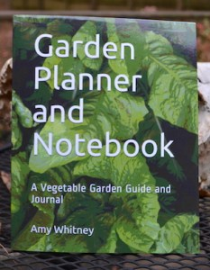 "Front cover of a book, with the title ""Garden planner and notebook"" on a background of green leaves."