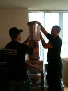 two men movers shrink-wrapping a carpet