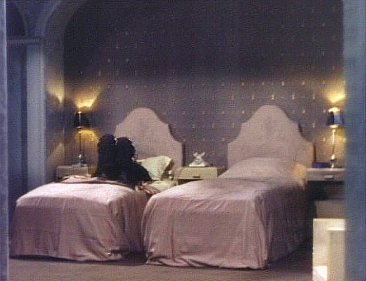 (above) This is the only frame that captured both beds with some of the architectural detailing. Were hotel rooms back then really this elaborate? I want that phone.