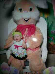 Little girl sitting on the Easter bunny's lap