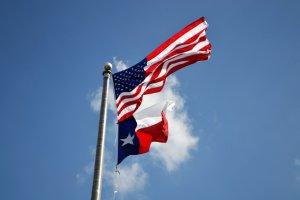 A flag of Texas on a pole next to a US flag.
