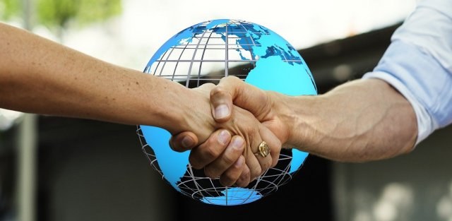 Movers Bellaire TX are shaking hands with you in front of a globe
