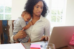 A mom carries a child while she works.