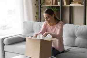 A woman packs a box.