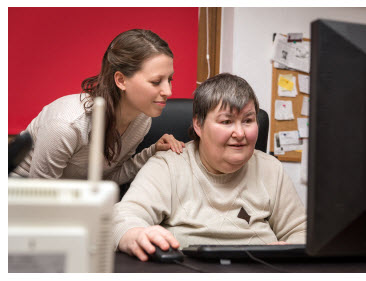 Snapshot of a woman assiting another womaon on an accessible workstation