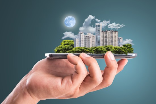 smart-city-illustration human hand carrying a miniaturized downtown urban area