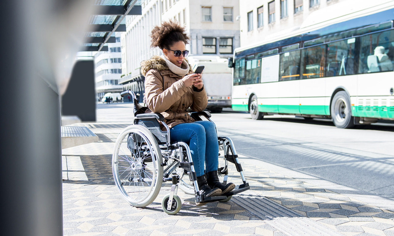 woman in wheelchair using her smart phone for wayfinding and accessible mapping