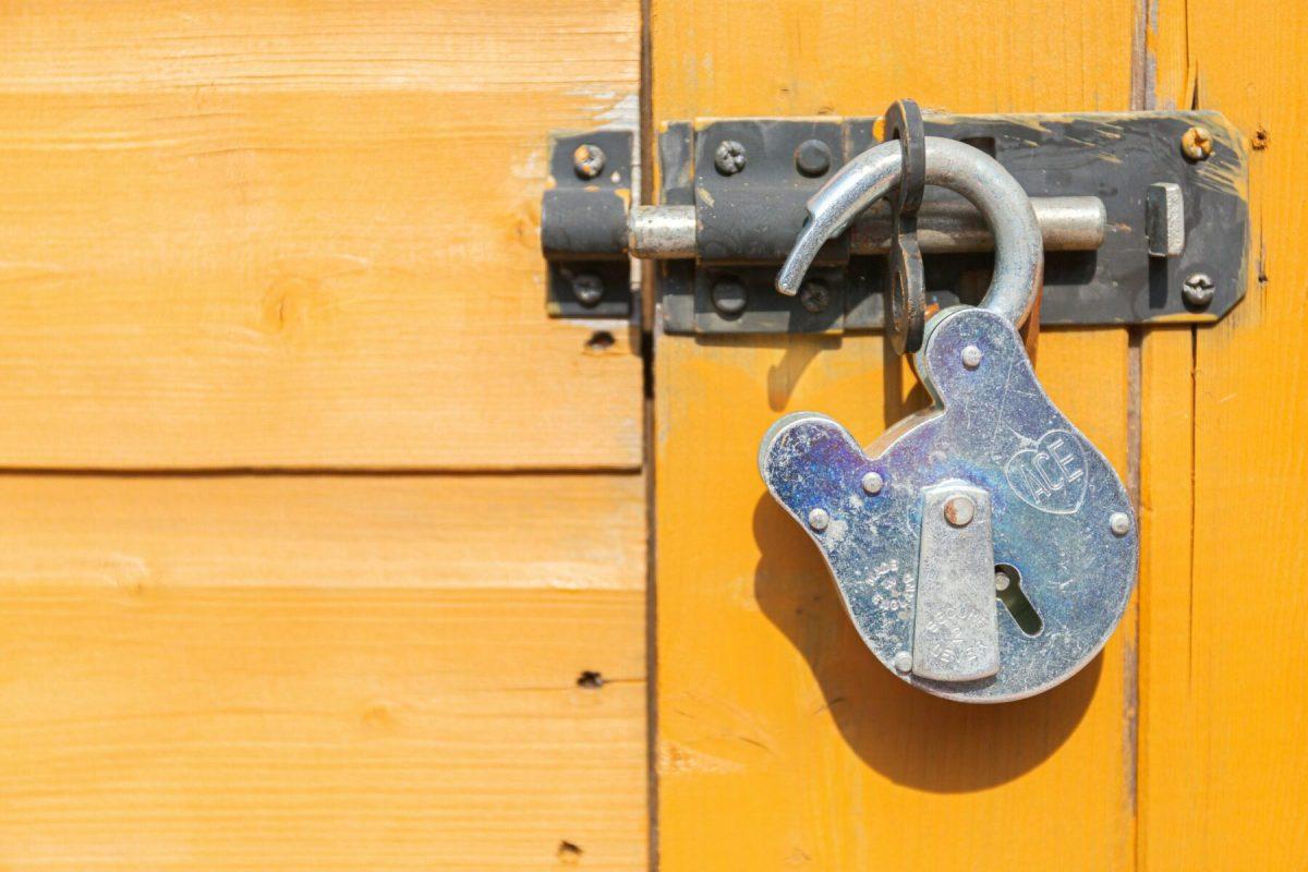 brown wooden door with padlock