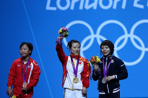 (120728) -- LONDON, July 28, 2012 (Xinhua) -- Gold medalist Wang Mingjuan (C) of China, silver medalist Hiromi Miyake (R) of Japan and bronze medalist Ryang Chun Hwa of the Democratic People's Republic of Korea attend the victory ceremony of women's 48kg weightlifting competition, at London 2012 Olympic Games in London, Britain, on July 28, 2012. (Xinhua/Chen Jianli) (nxl)
