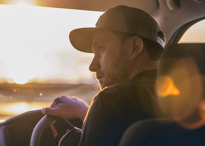 man driving sunrise road trip