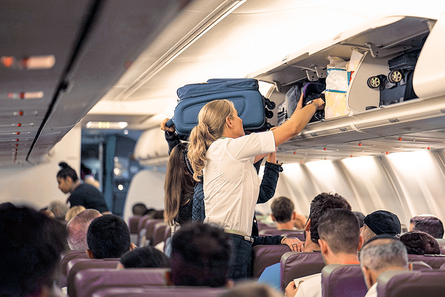 stewardess helps the passengers to put their luggage in the cabin of the plane