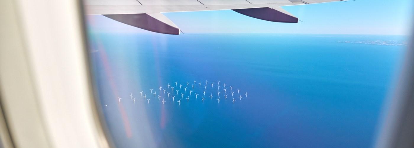 airplane flying over an ocean wind farm