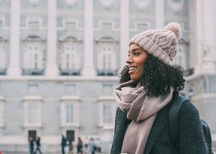 Young black woman drinking coffee wandering in the streets of Madrid on winter tourist