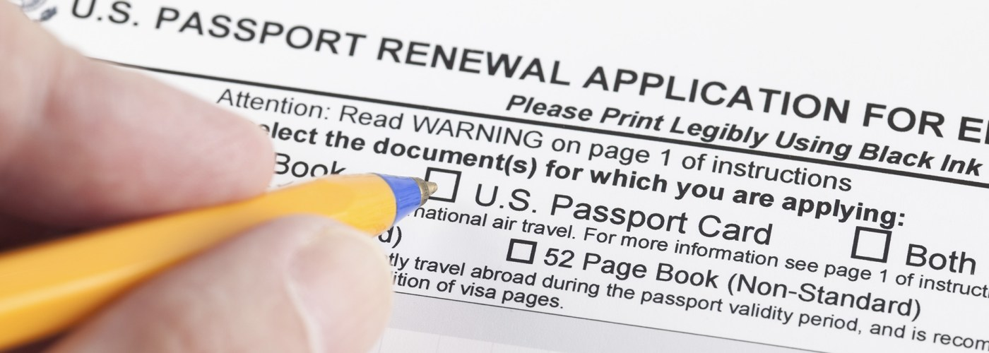 hands pencil filling out passport renewal application