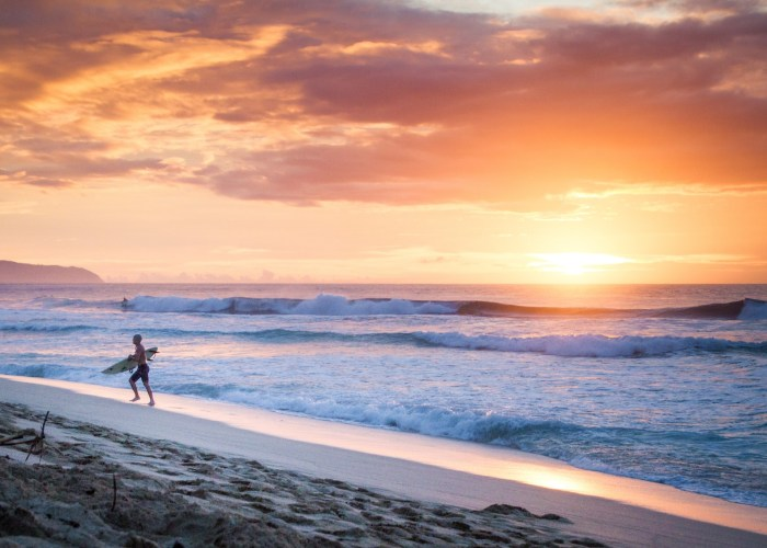 surfer on beach at sunset in Hawaii