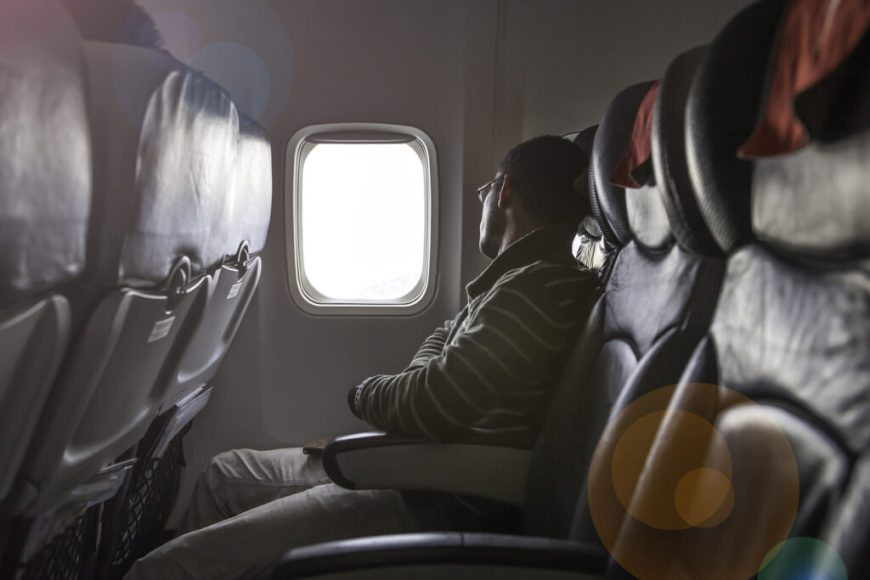 man sitting next to empty comfort seat on the plane.