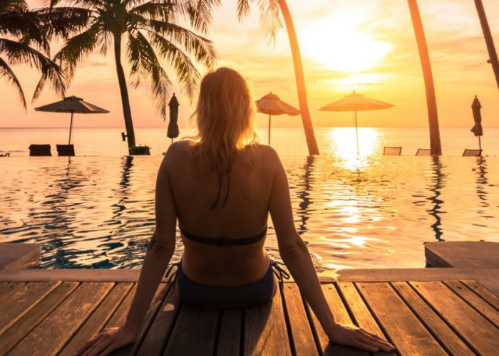 woman sitting at sunset at tropical resort.