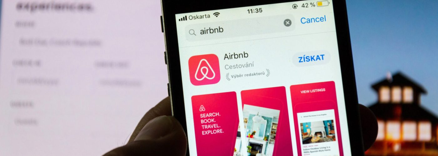 Airbnb logo and app on phone.