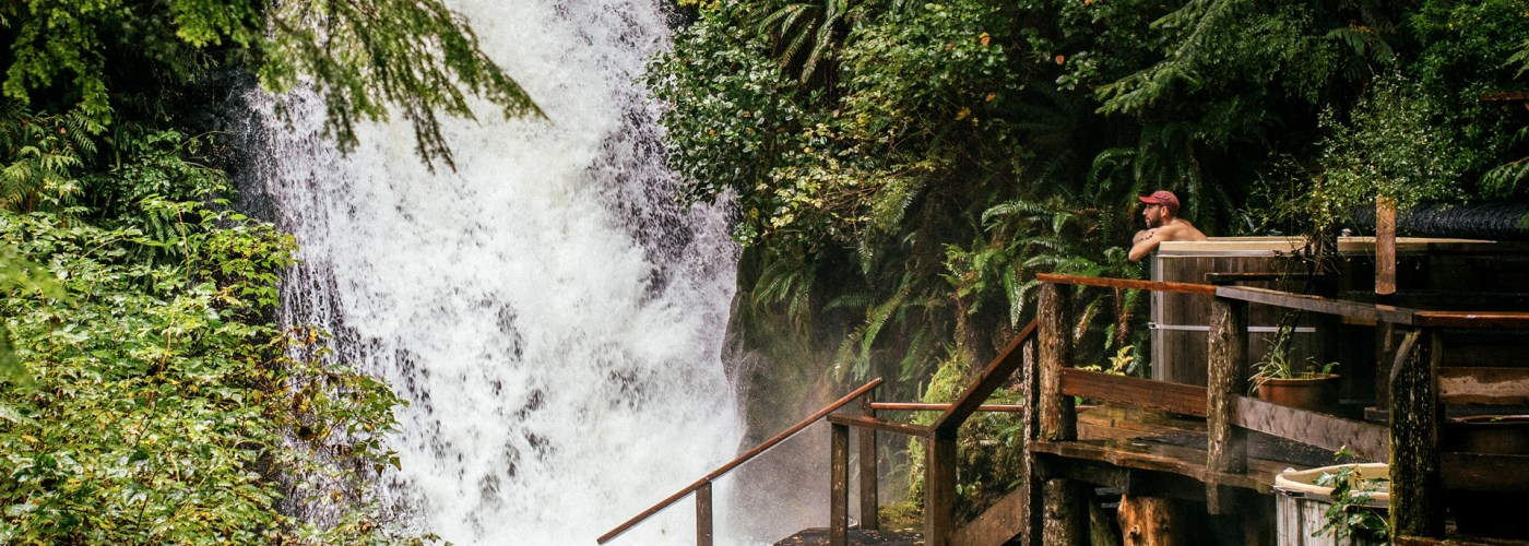 man sits in hot tub by waterfall in Nimmo Bay Wilderness Resort
