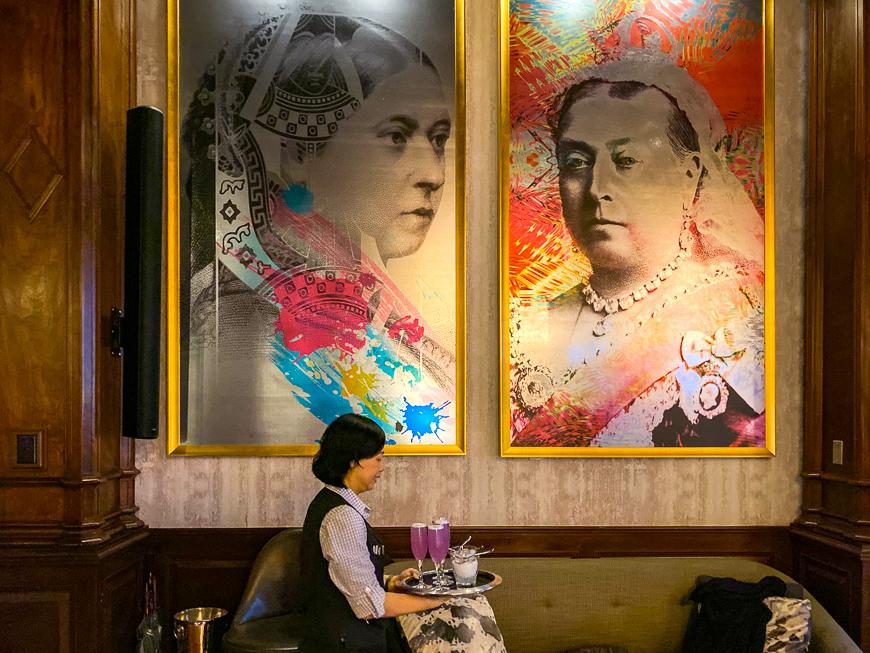server walks past two portraits of Queen Victoria in British Columbia, Canada