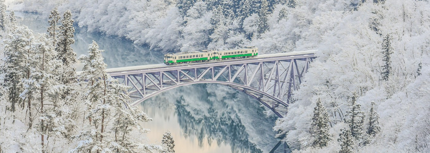 train passing over bridge in japan winter backdrop