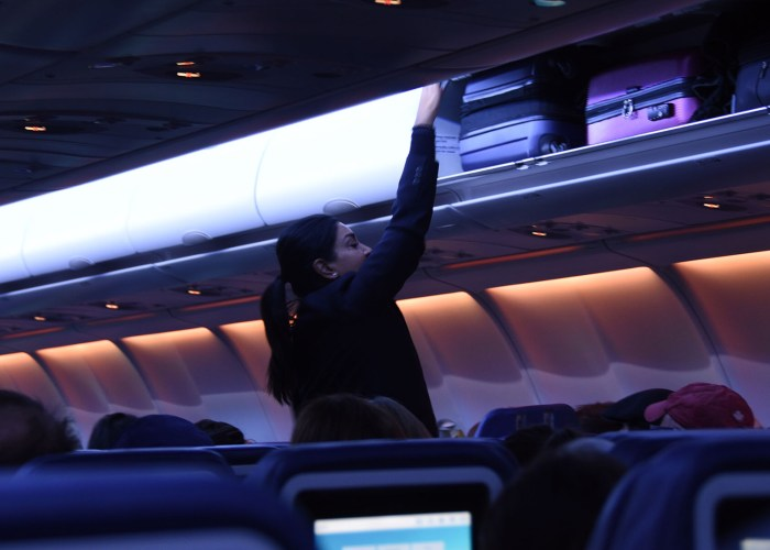 flight attendant closing overhead bin.