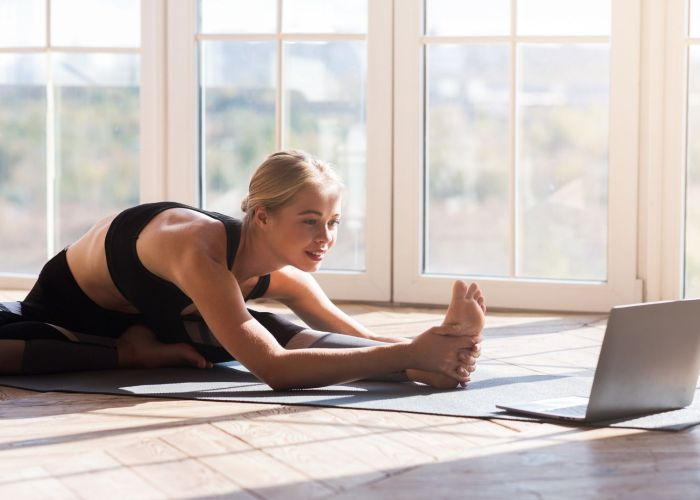 Woman streaming a workout on a laptop at home
