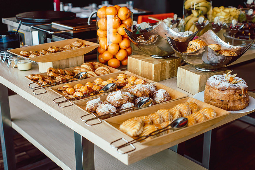 Assortment of fresh pastry and mandarin on table in buffet.