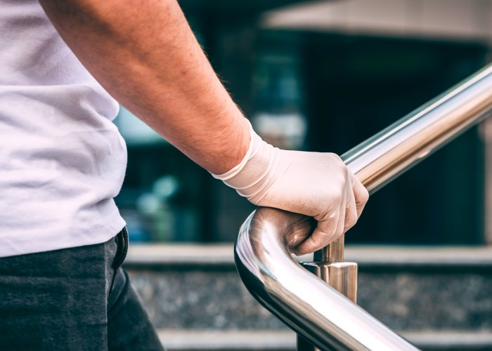 Male hand in a white latex medical glove on the railing. man wearing protective latex gloves touching railing outside