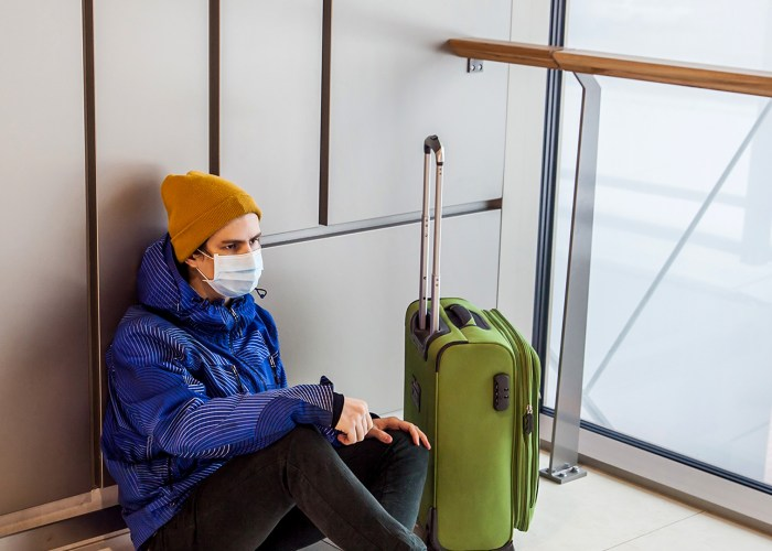 boy with a green suitcase is sitting on floor in waiting area wearing protection mask