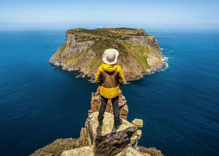 young man trekking coast tasmania australia.