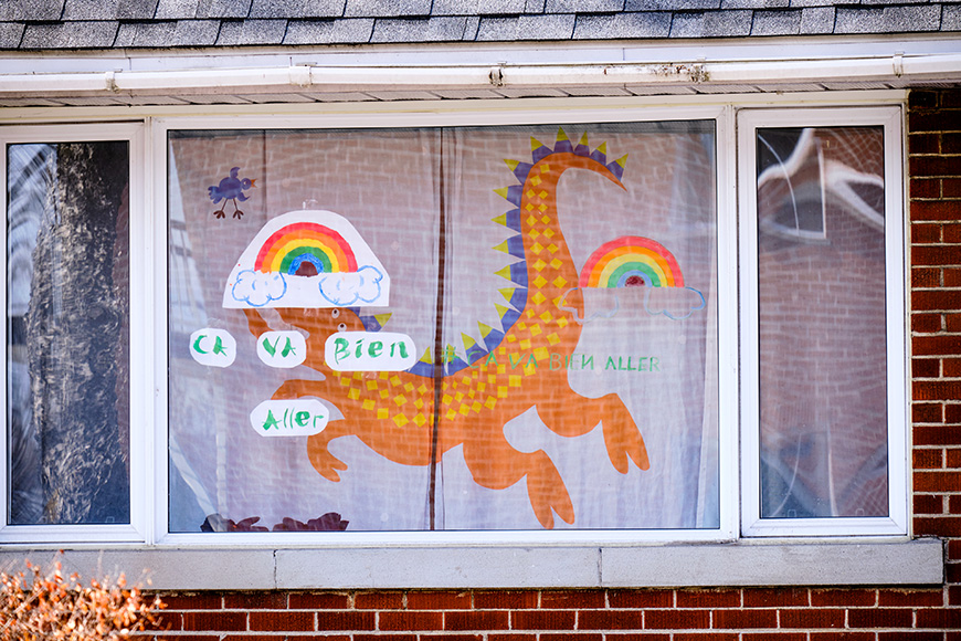"""House window with rainbow drawings and slogan """"Ca va bien Aller"""" as message of hope in Montreal part of """"It's going to be OK"""" movement during CoVID19 epidemic"""