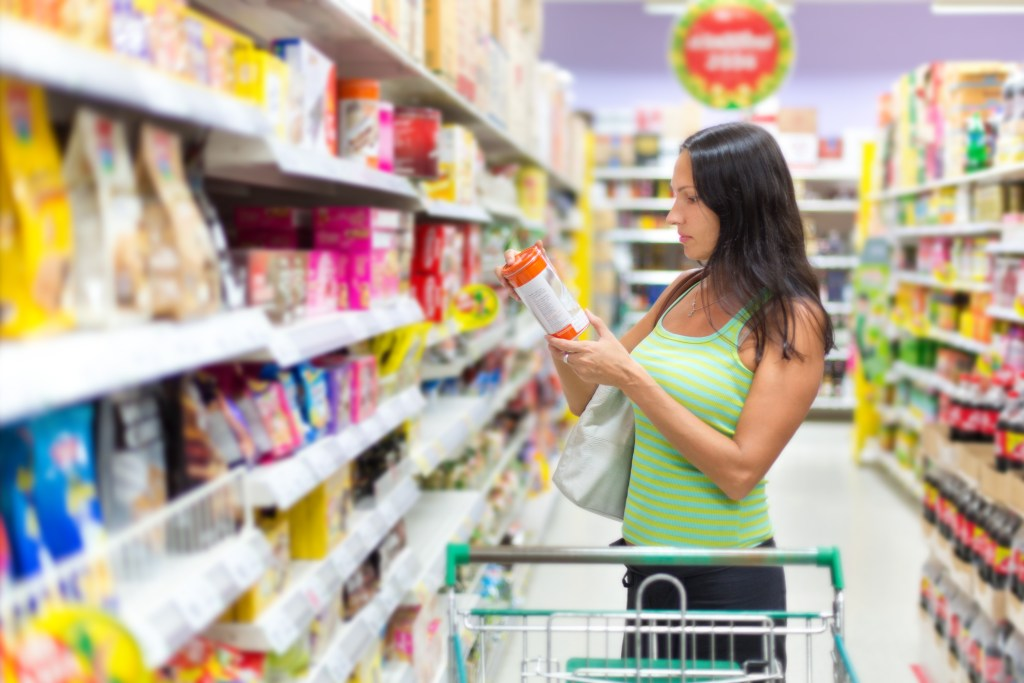Woman reading package of food in a grocery store