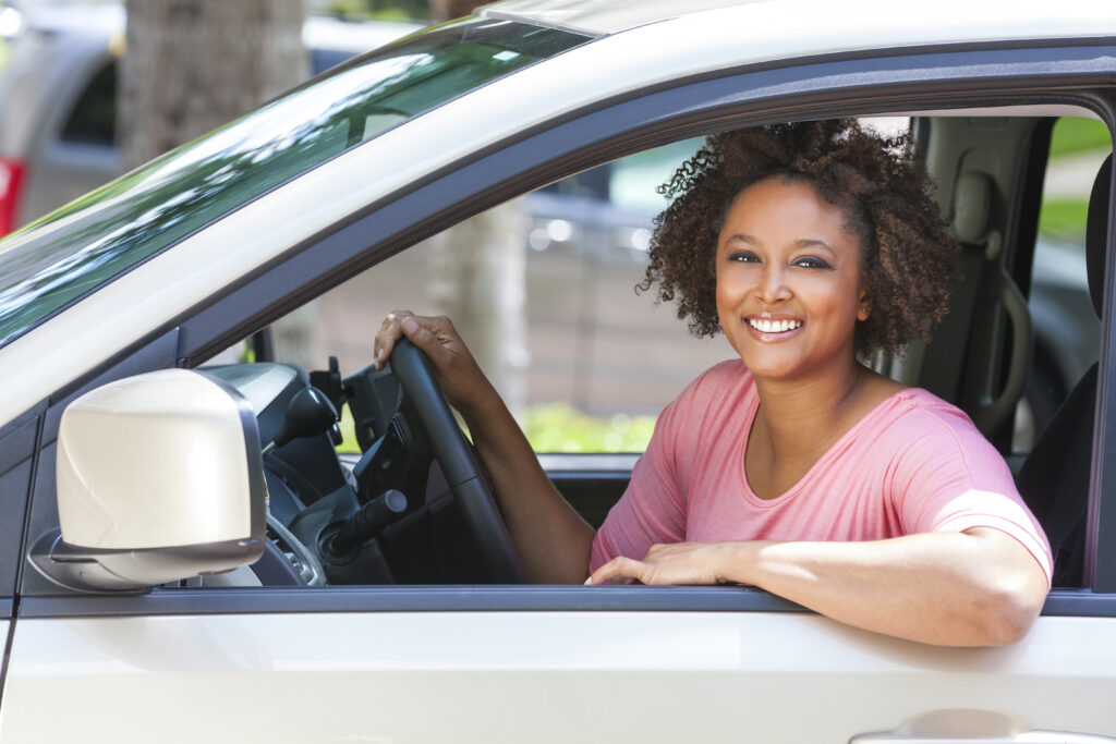 Woman smiling while sitting behind wheel of car.