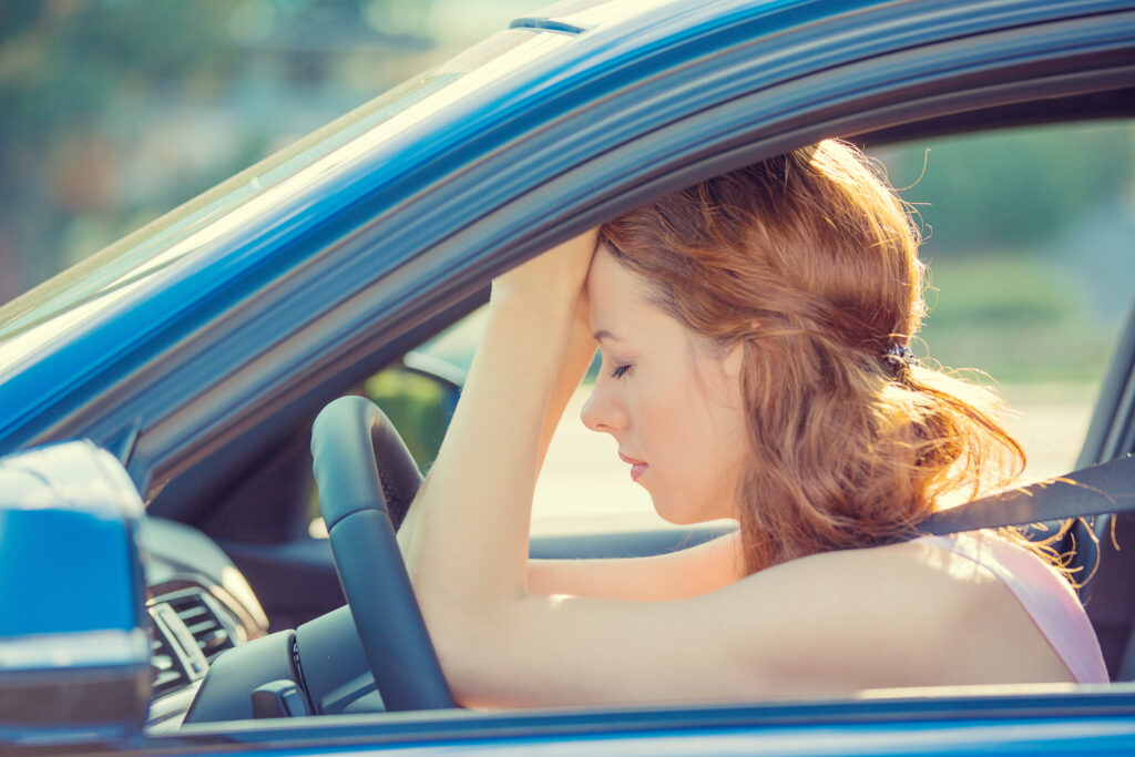 Woman looking frustrated in car, with head in hands, leaning against steering wheel.
