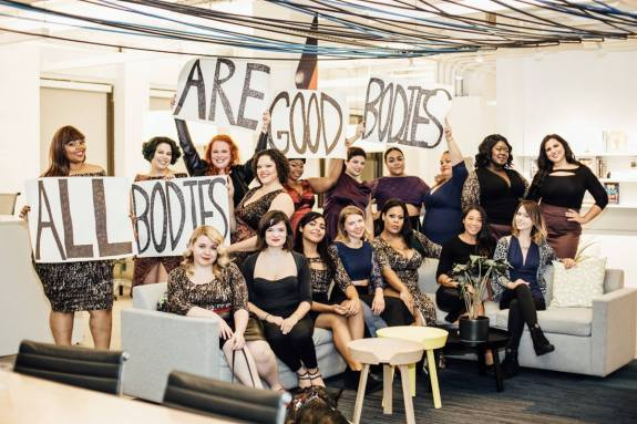 diverse women holding signs saying all bodies are good bodies