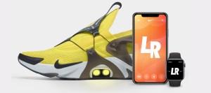 Et par Nike Adapt Huarache i gult og sort, ved siden av en iPhone og Apple Watch.