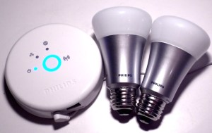En Philips Hue-hub og to LED-lyspærer. Philips Hue er hvit og rundt med en knapp i midten.