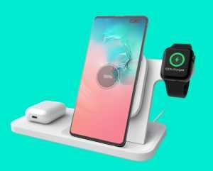 Tre i en-lader med et AirPod-etui på en plate, en mobil på et stativ og en iWatch som henger rundt en arm på stativet.
