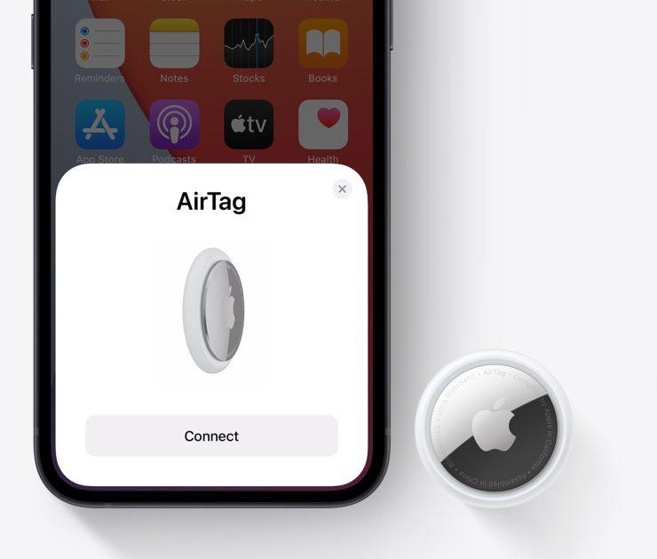 En AirTag, formet som en knapp, ved siden av en iPhone som er i ferd med å kobles til AirTagen.