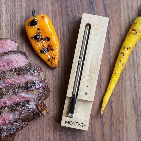 Et Meater plus-termometer med grillet kjøtt og grønnsaker