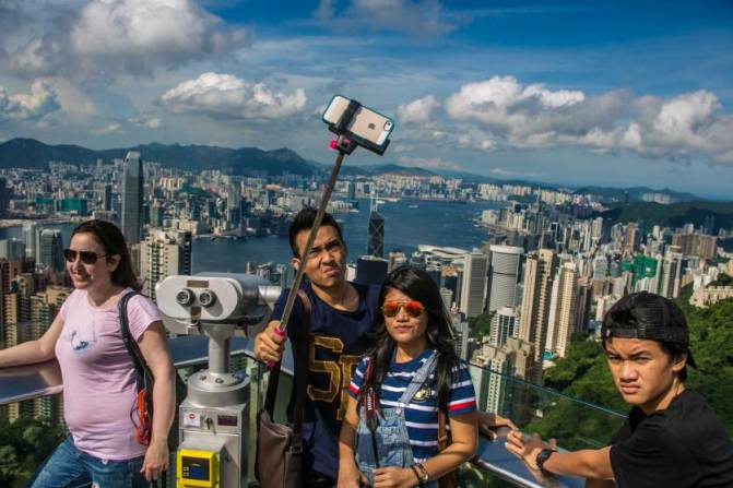 HONG KONG - MAY 25: A group of people takes a picture of themselves from the Victoria Peak Lookout with the Hong Kong skyline as a backdrop on May 25, 2014, in Hong Kong, China. Hong Kong, with a population of nearly 8 million people, has become one of the world's most important trade and financial centers since the British relinquished control of the region in 1997 to the People's Republic of China. (Photo by George Rose/Getty Images)