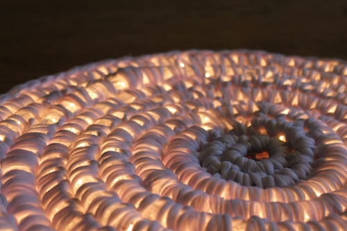Crocheting around rope light to make an outdoor floor light. So neat!