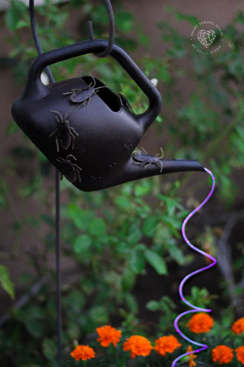 Halloween Watering Can with purple cascading lights and bugs.
