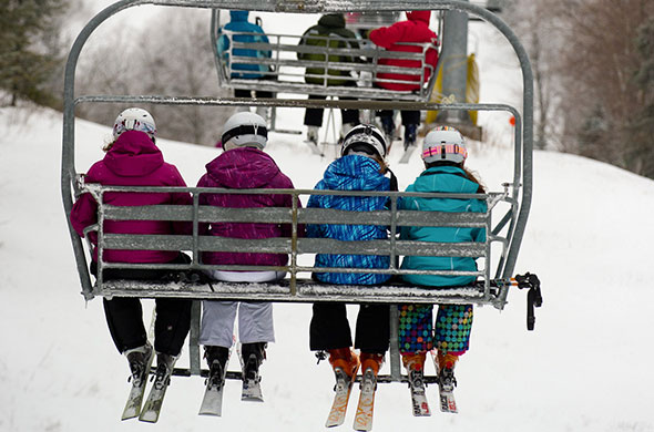 Skiers sit on chair lift going up the ski mountain.