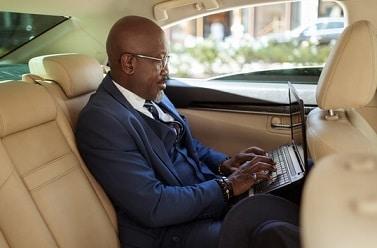 Black businessman in back of car