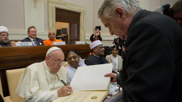 Signing up: Pope Francis signs a joint Declaration of Religious Leaders against Modern Slavery, at the Vatican as Andrew Forrest watches on.